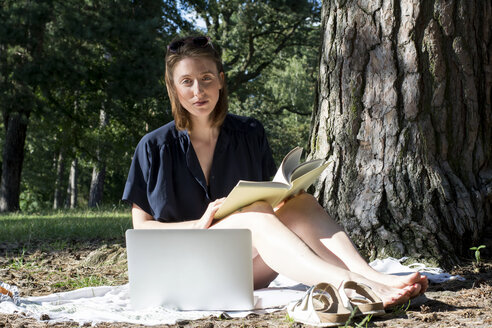 Young woman sitting under a tree with a book and a laptop - LMF00746