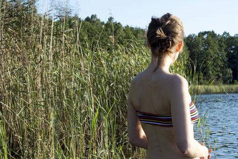 Young woman enjoying the sun at a lake - LMF00767