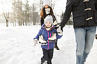 Little girl going ice skating with her parents - HAPF02097