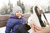 Mother helping daughter to put on her ice skates - HAPF02103