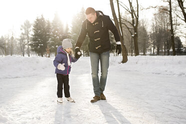Father and daughter ice skating on frozen lake - HAPF02106