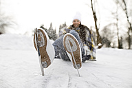 Woman with ice skates lying on snow - HAPF02121