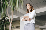 Businesswoman standing in office, holding laptop - KNSF02718