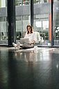 Businesswoman sitting on ground in empty office, using laptop - KNSF02724