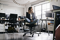 Businesswoman sitting cross-legged on an office chair - KNSF02751