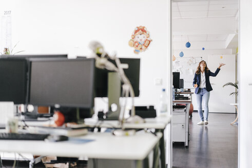 Happy businesswoman juggling balls in office - KNSF02754