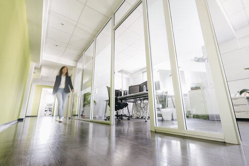 Businesswoman walking in corridor of office building - KNSF02760