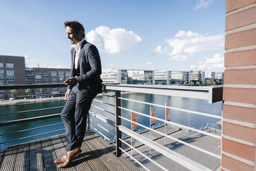 Businessman standing on balcony, holding smartphone - KNSF02775