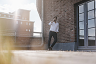 Businessman standing on rooftop terrace, making a phone call - KNSF02790