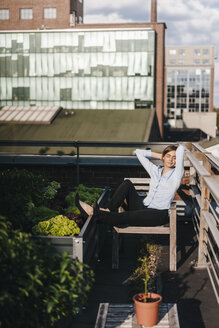 Businesswoman relaxing in his urban rooftop garden - KNSF02793