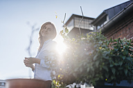 Businesswoman standing on her urban rooftop garden - KNSF02799