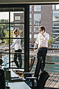 Businessman and woman standing on balcony,  man making a phone call - KNSF02805