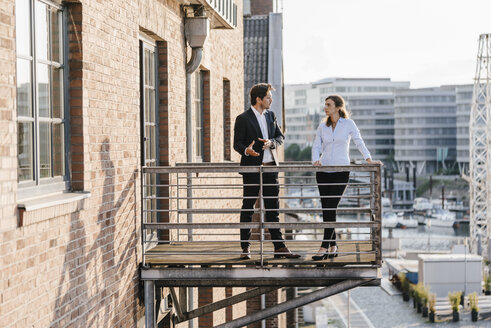 Business people standing on balcony, discussing - KNSF02808