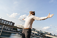 Happy businessman standing on balcony, with arms out - KNSF02814