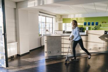 Businesswoman using kickboard in office - KNSF02817