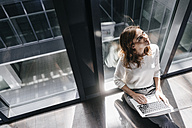Businesswoman sitting on ground in empty office, using laptop - KNSF02829
