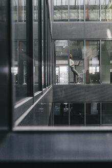Woman standing at office window - KNSF02838