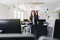 Happy businesswoman juggling balls in office - KNSF02841