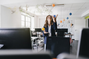 Happy businesswoman juggling balls in office - KNSF02841