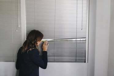 Woman standing by window, spying through blinds - KNSF02850