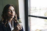 Businesswoman drinking from a straw, sticking in a cactus pot - KNSF02853