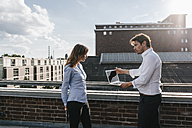Business people standing on balcony, discussing, using laptop - KNSF02859