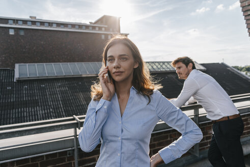 Business people standing on balcony, using smartphone - KNSF02862