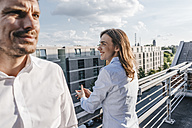 Business people standing on balcony - KNSF02865