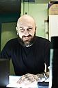 Portrait of confident tattoo artist in studio - IGGF00160