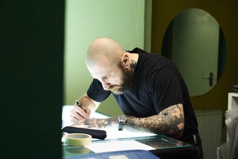Tattoo artist designing motif on light table in studio - IGGF00163