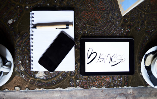 Still life with cell phone, tablet, pen and notebook on an antique table - IGGF00172