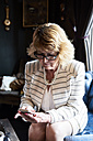 Senior businesswoman sitting on couch checking cell phone - IGGF00178