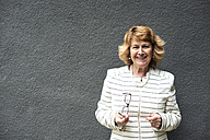 Portrait of smiling senior businesswoman against grey wall - IGGF00181