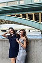 UK, London, two women with smartphone at banks of the Thames River - MGOF03605