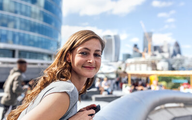 UK, London, portrait of smiling woman in the city - MGOF03608