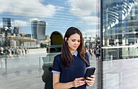 UK, London, woman checking her smartphone in the city - MGOF03611