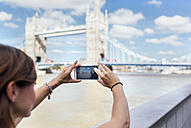 UK, London, woman taking a picture of the Tower Bridge - MGOF03614
