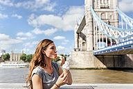 UK, London, woman eating an ice cream near the Tower Bridge - MGOF03620