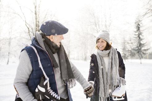 Senior couple with ice skates walking in winter landscape - HAPF02127