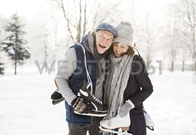 Happy senior couple with ice skates in winter landscape - HAPF02130