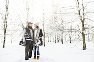 Senior couple with ice skates in winter forest - HAPF02139