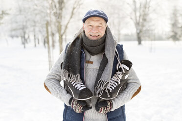 Smiling senior man with ice skates in winter forest - HAPF02142