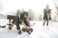 Senior man sitting on bench in winter landscape putting on ice skates - HAPF02148