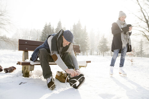Senior man sitting on bench in winter landscape putting on ice skates - HAPF02148