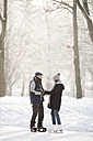 Senior couple with ice skates standing on frozen lake - HAPF02151