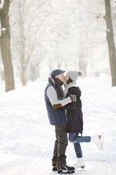 Senior couple hugging and kissing on frozen lake - HAPF02154