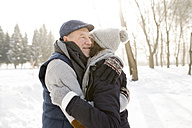 Happy senior couple hugging in winter landscape - HAPF02166
