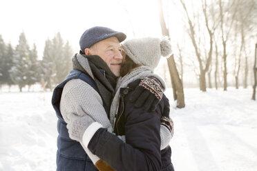 Happy senior couple hugging in winter landscape - HAPF02166