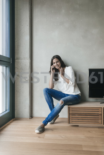 Portrait of smiling woman on cell phone at home - JOSF01563 - Joseffson/Westend61