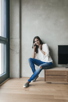 Portrait of smiling woman on cell phone at home - JOSF01563